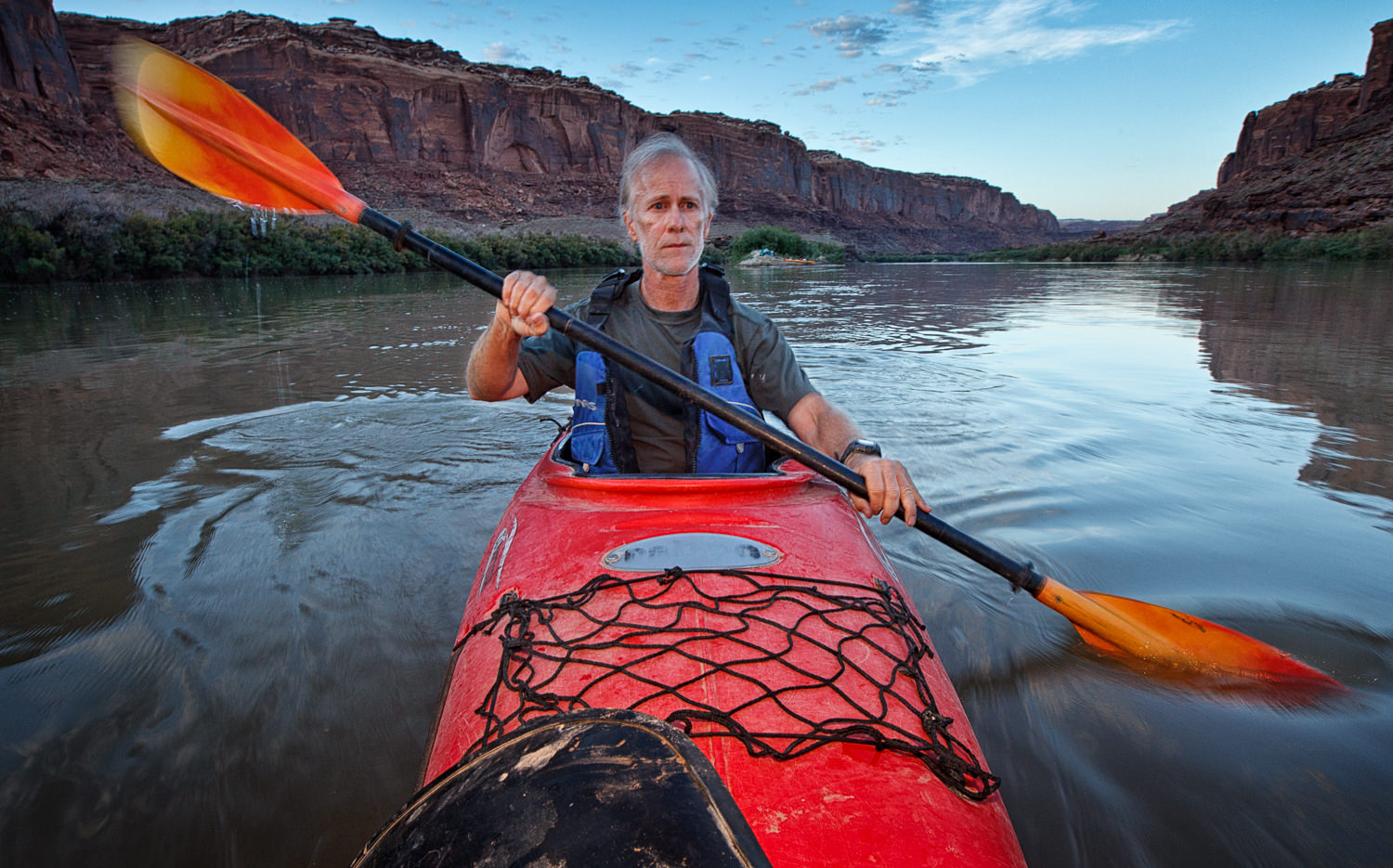I clamped a Canon 5DMII with a flash and warming filter to the front of my kayak and then went paddling off around sunset. I purposely used a slower shutter speed to get a little blur in the paddles.