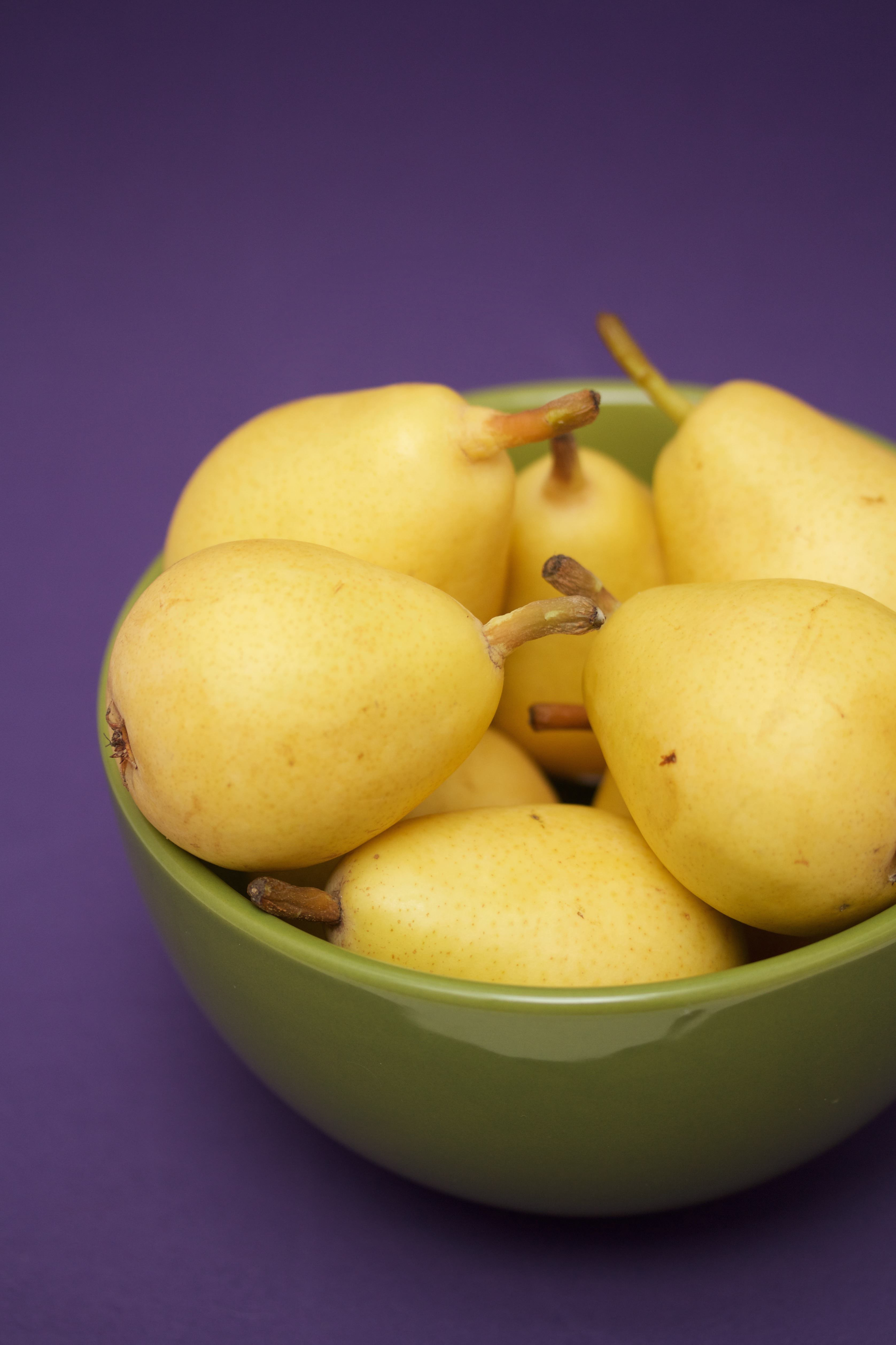 Yellow pears in a green bowl on a purple background