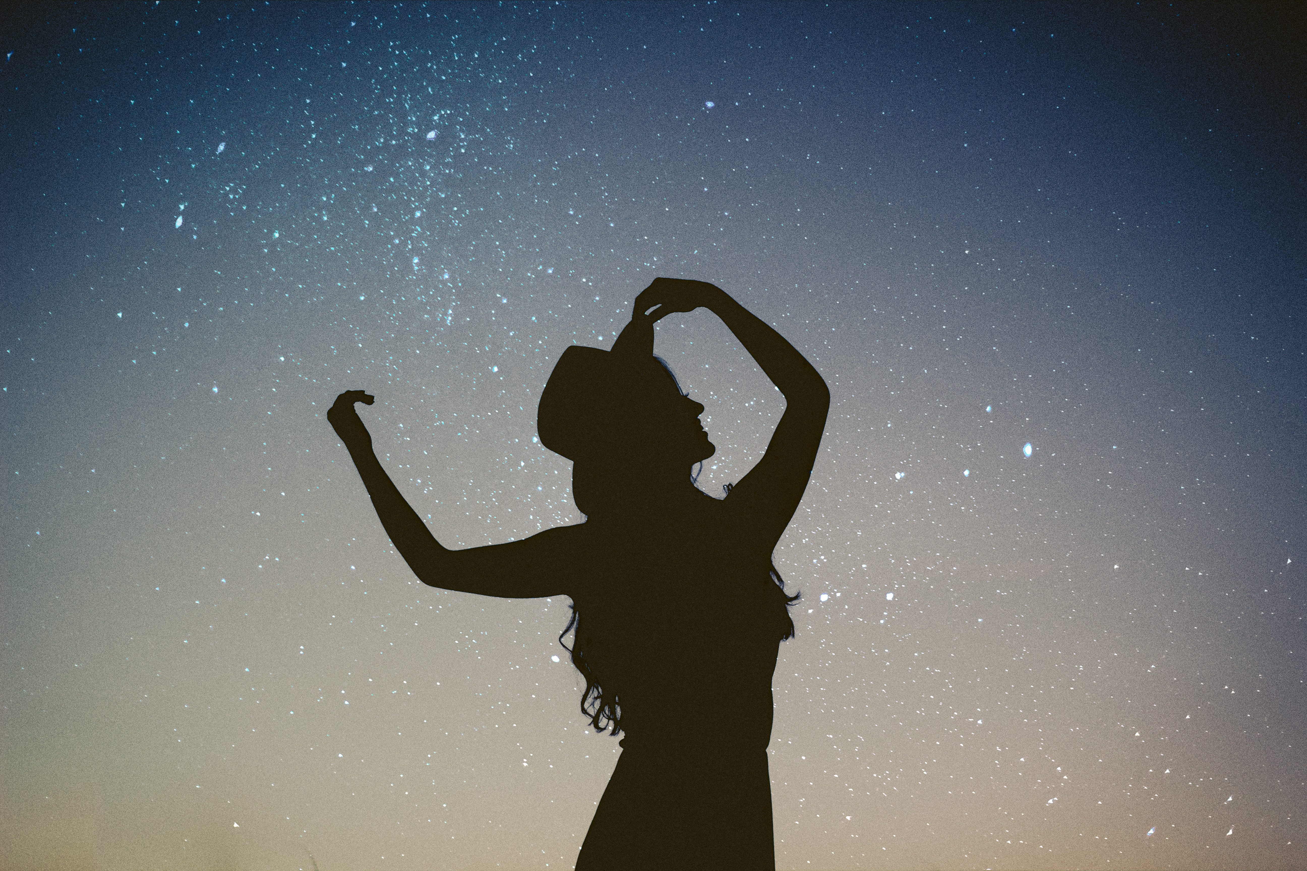 silhouette of girl against nightsky