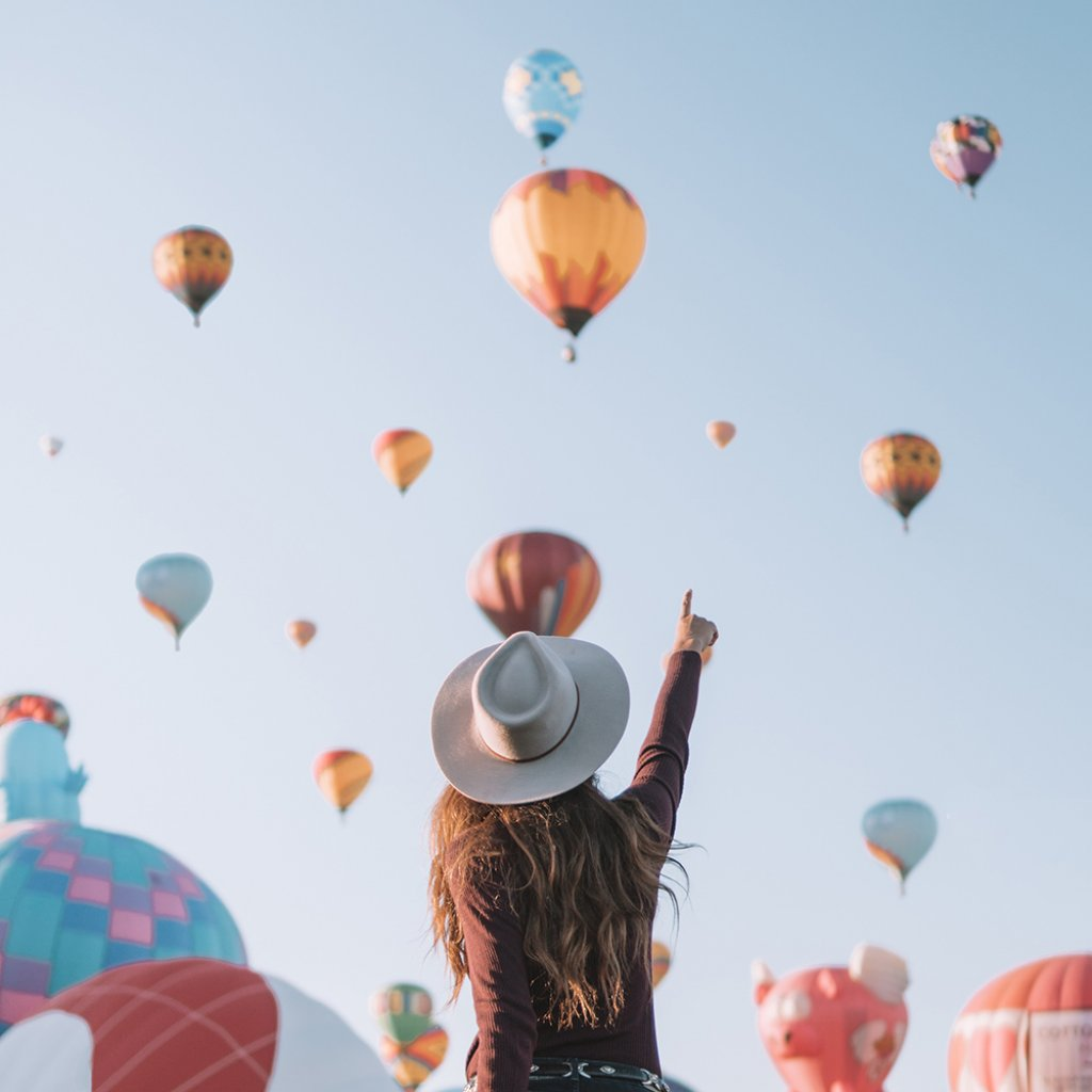 girl pointing at hot air balloons