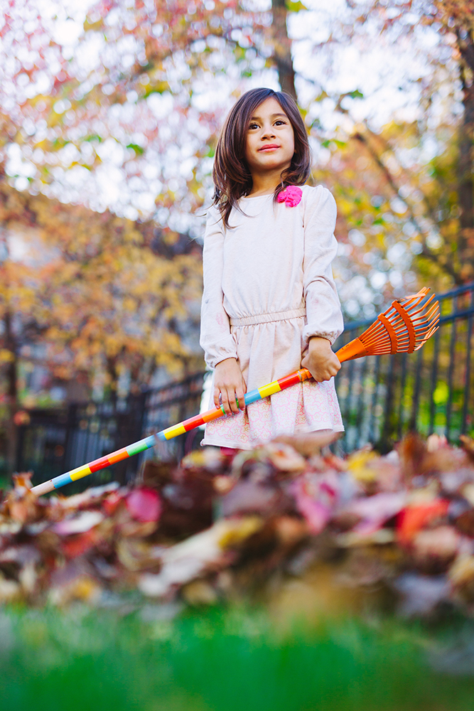 little girl holding rake and posing